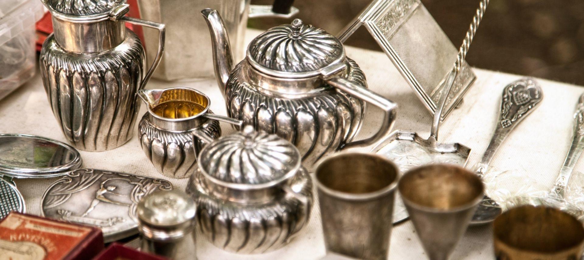 Antique silver, tea pots, cups on a table