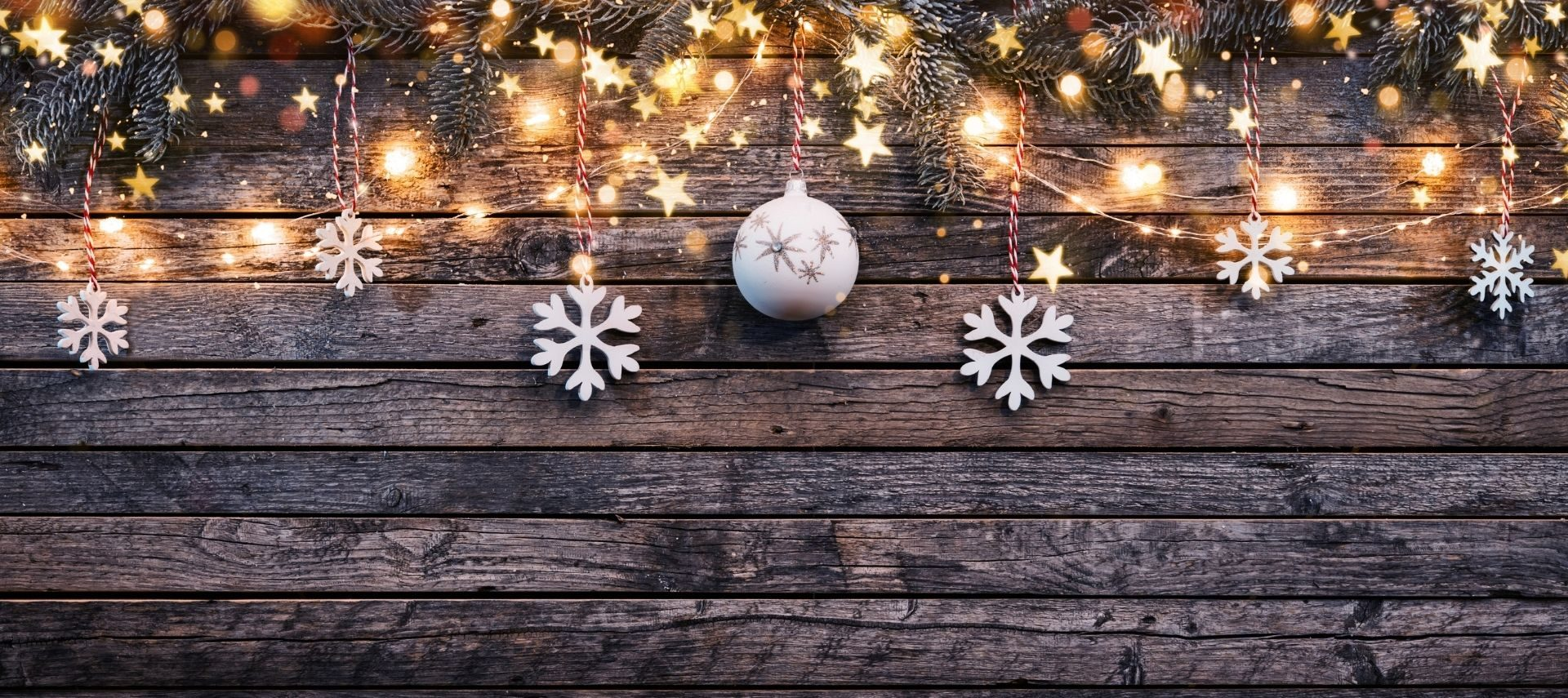 Christmas lights and decorations against a weathered wood backdrop