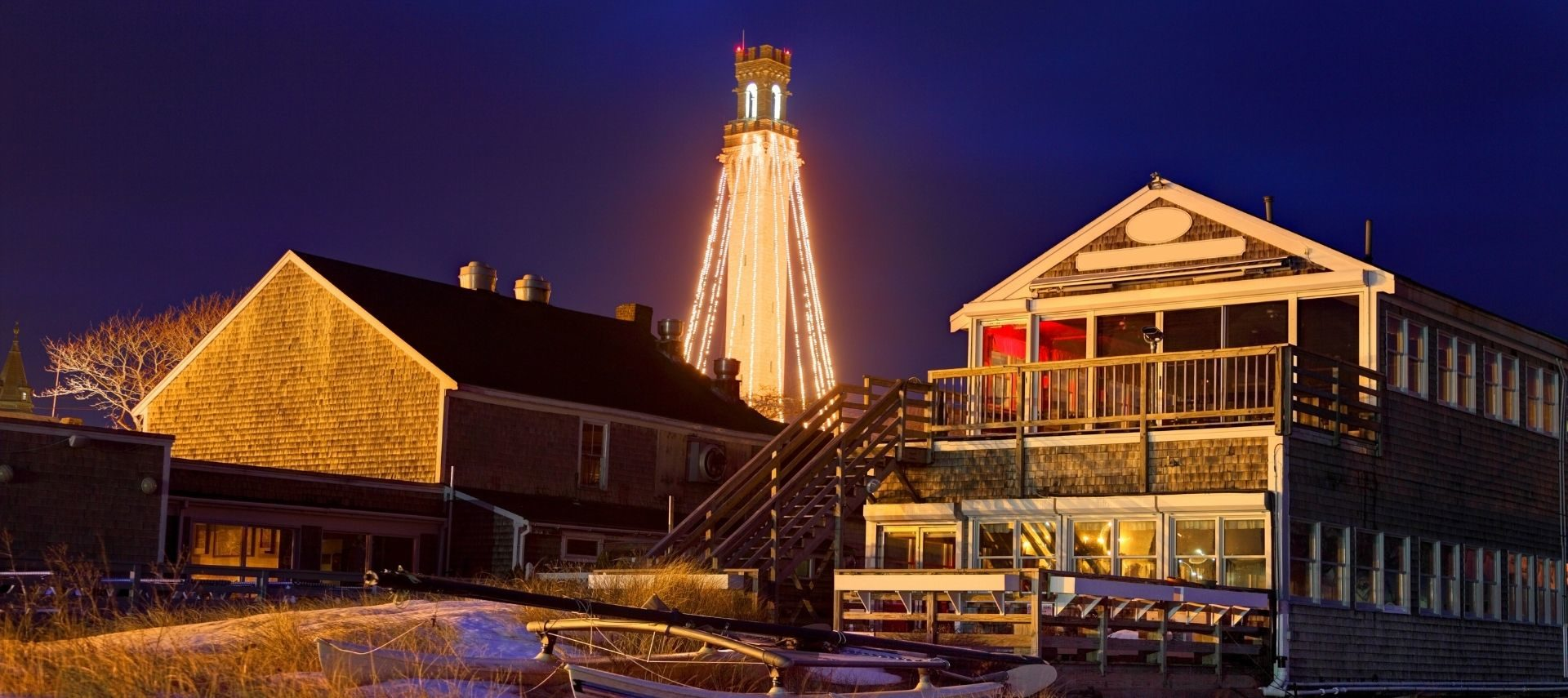Holiday lights twinkling at night behind a row of beach houses on Cape Cod