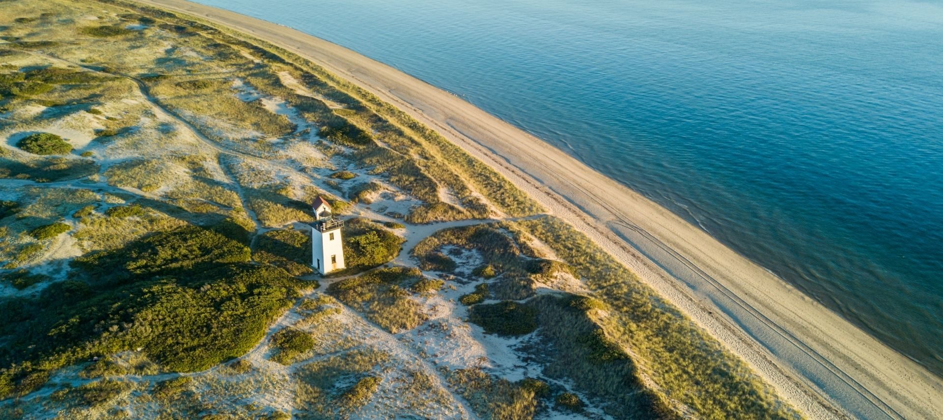 Aerial view of Cape Cod, a winding road that follows the curve of the island and the beach with a lighthouse.