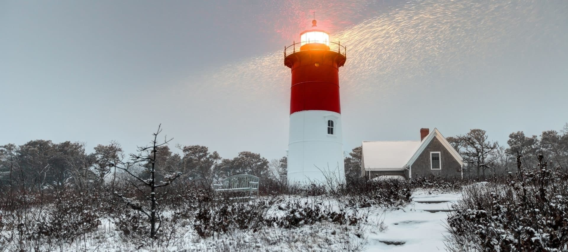 Nauseat Lighthouse during the winter on Cape Cod with sun rays shining down