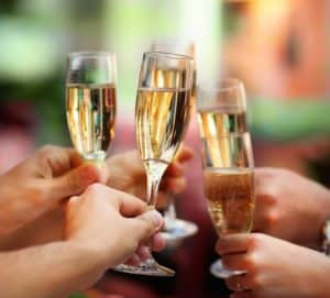 people toasting 4 glasses of champagne