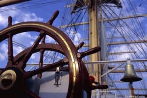 historic ship wheel and sail