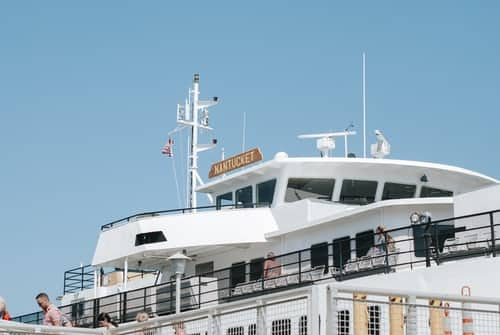 White ferry boat with black railings against a blue sky with Nantucket on its masthead.