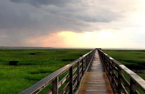 View of a long wooden dock over grassy marsh land heading towards the ocean with stormy clouds off in the sky