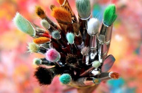 View of the tops of many different paintbrushes in a cup with many different rainbow colors in the background