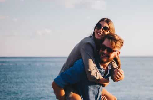 Man holding a woman on his back laughing with sunglasses on and the ocean behind them