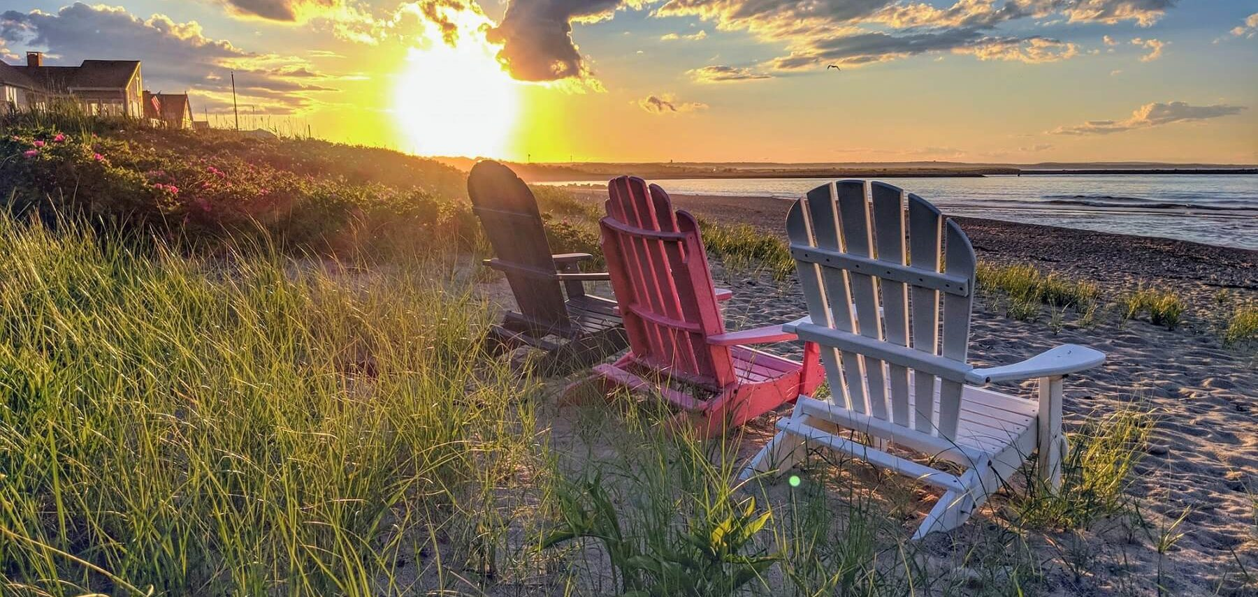 Adirondack chairs on a Cape Cod beach at sunset