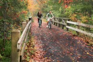 couple riding bikes along a leaf strewn bike path