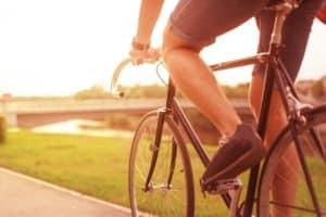 leg of man riding a bike olong a paved bike trail
