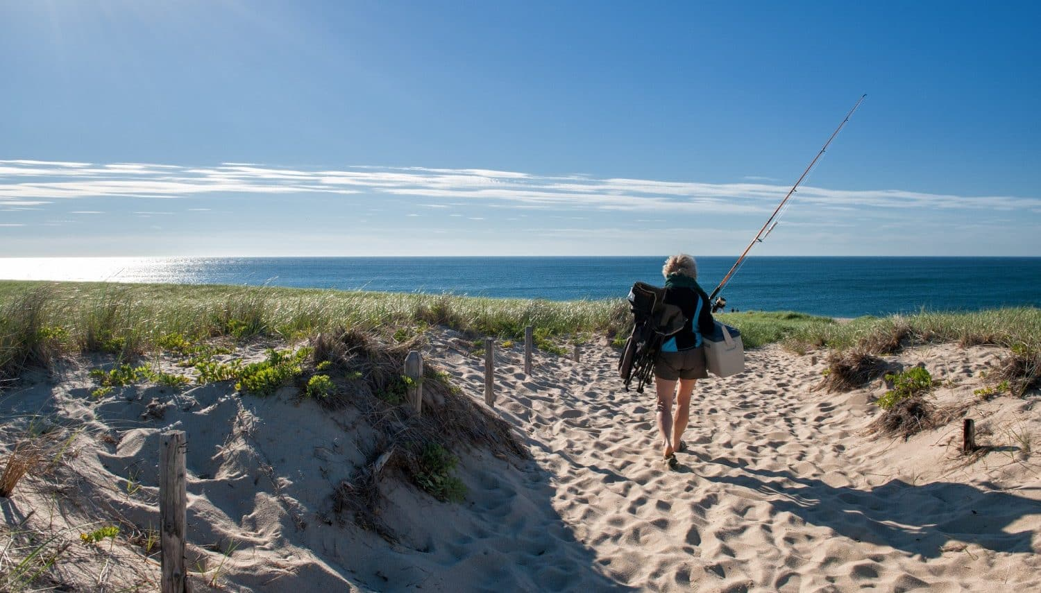 A woman carrying fishing poles to a cape cod beach