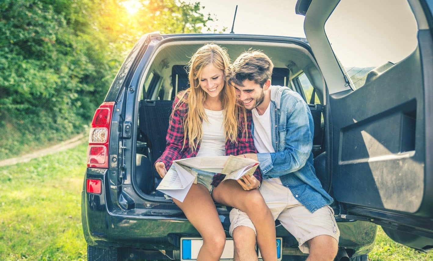 Couple in a car going over their Cape Cod road trip itinerary