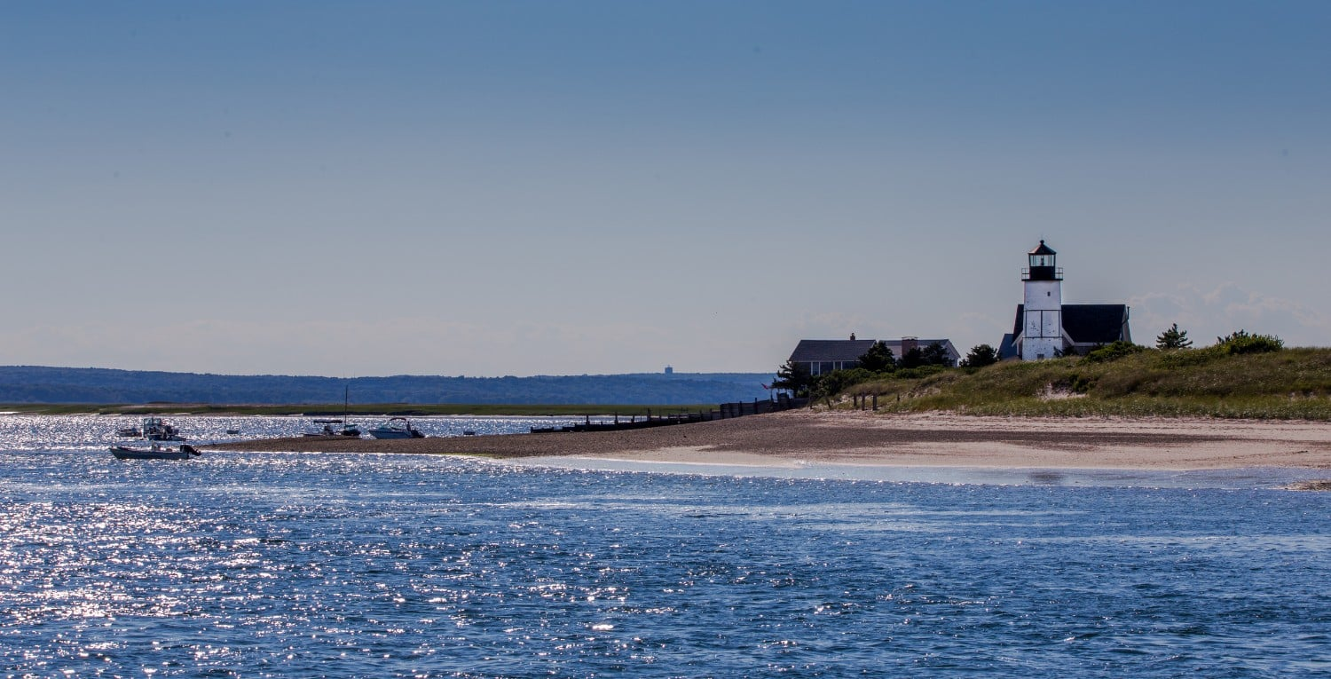 Sandy Neck Lighthouse near Barnstable, MA with calm seas and blue skies