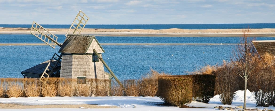 Old windmill near blue ocean with brown bushes and snow on the ground