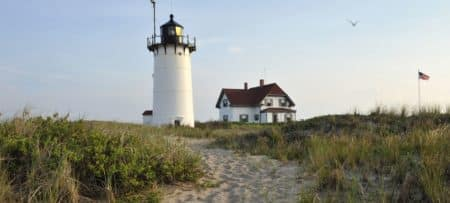 White lighthouse next to a two-story white gabled house on the beach