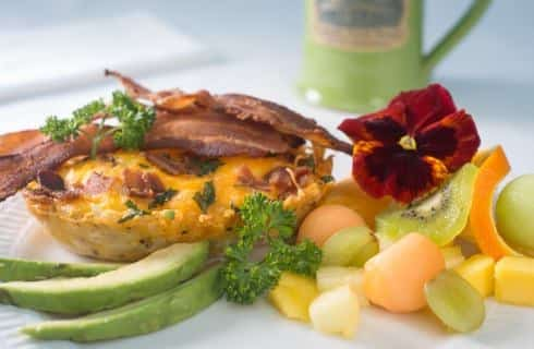 Egg and bacon quiche dish, bacon strips, sliced avocado, and fresh fruit on white porcelain plate