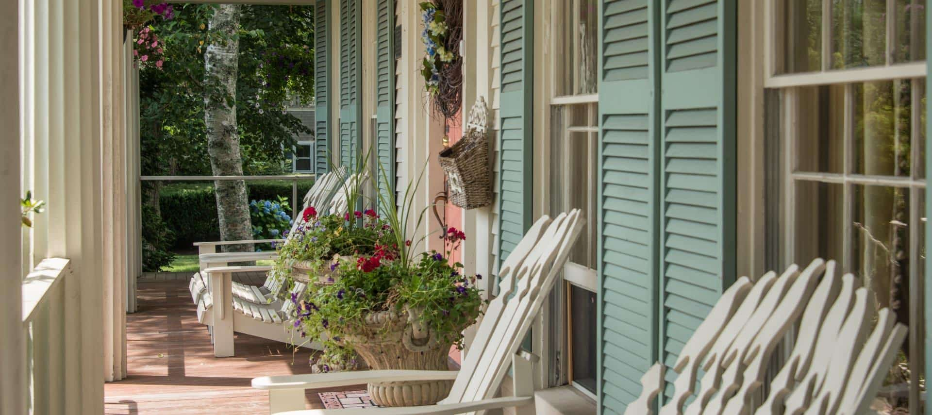 Front porch with multiple cream colored Adirondack chairs, potted planters with pink and purple flowers, salmon colored front door, and light green shutters