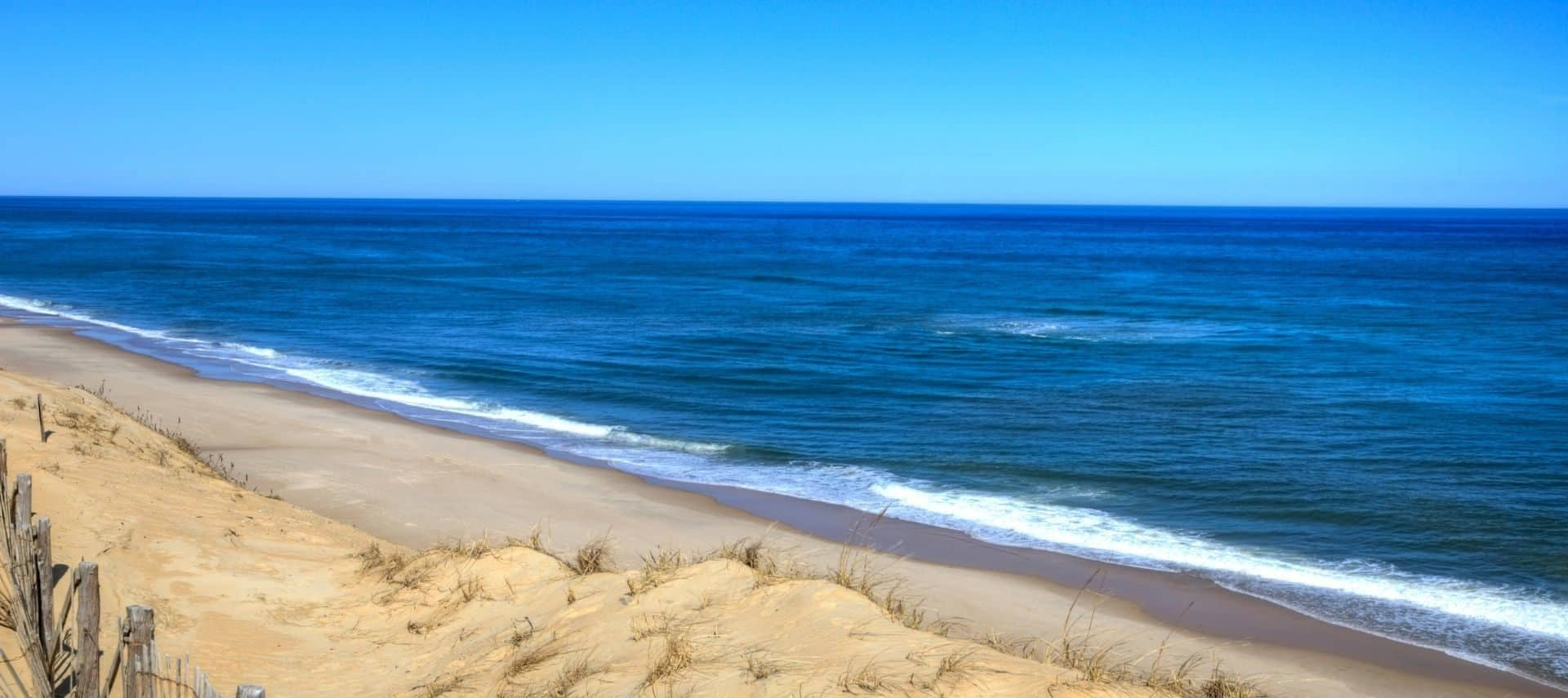 Cape Cod National Seashore with sandy beach, deep blue waters, and bright blue sky