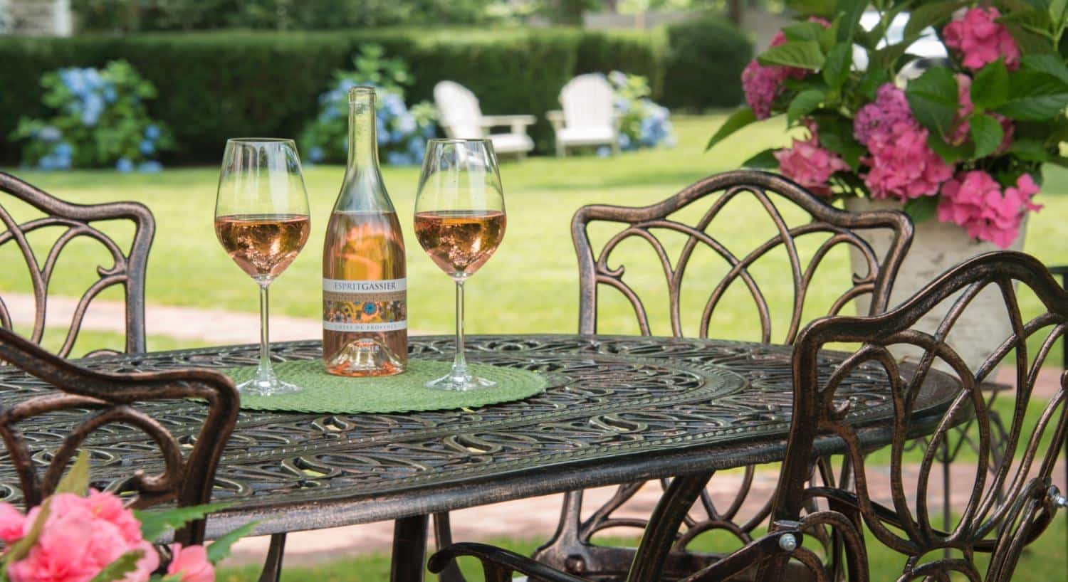 Rod iron patio table and chairs with wine bottle and two wine glasses full of wine on top
