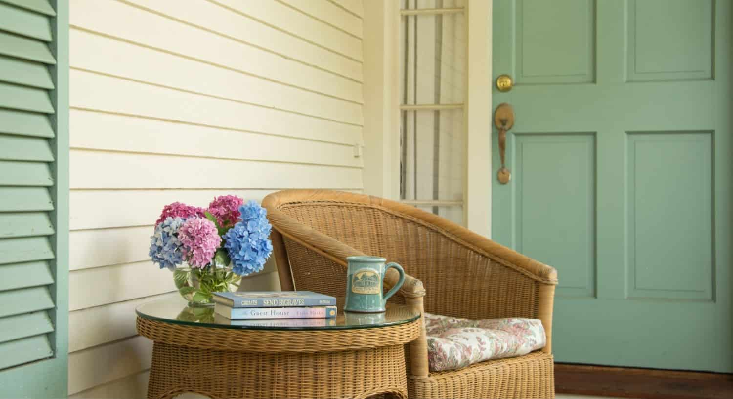 Light brown wicker chair with light paisley cushion next to light brown wicker coffee table with glass top with glass vase, pink and blue flowers, coffe mug, and books sitting on top