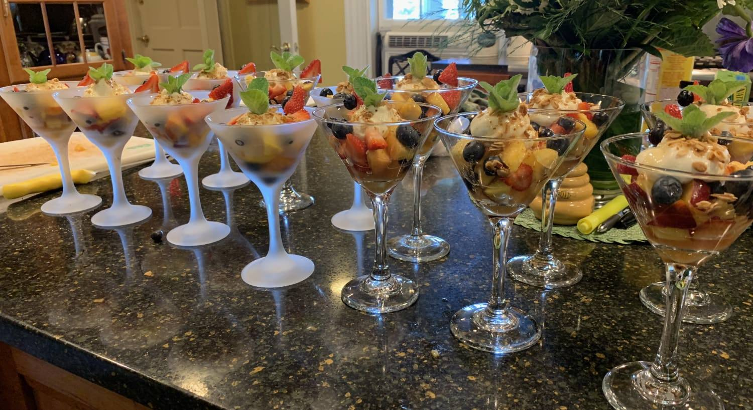 Clear and frosted martini glasses filled with fruit and yogurt topped with a few mint leaves