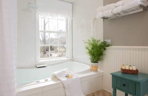 Bathroom with white wooden paneling on the walls, white tile on walls around shower with large white tub, and white shower curtain