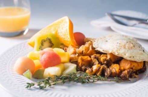 Sweet potato hash with sausage crumbles topped with an over medium fried egg with a side of fruit on white porcelain plate