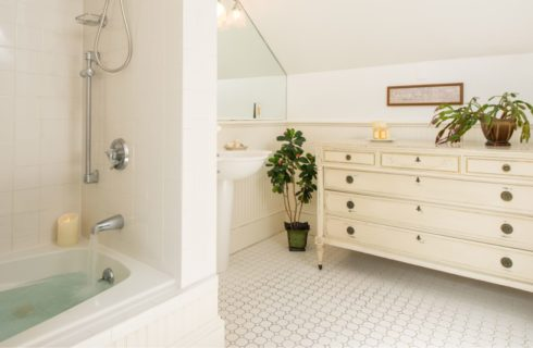 Bathroom with antique cream colored dresser, white pedestal sink, and shower and tub combo unit surrounded by white tile
