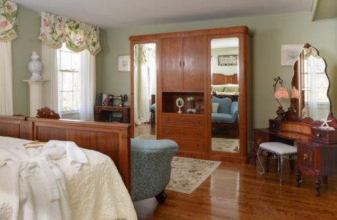 Bedroom with large dark wooden armoir with dual mirrors, antique sewing machine in the corner, and vintage makeup desk with mirror and rod iron bench