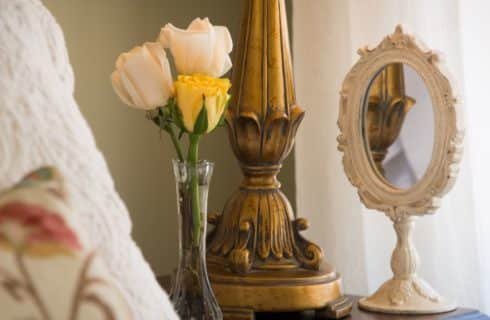 Close up view of glass vase with white and yellow roses, ornate gold lamp, and ornate white hand held mirror