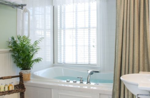 Bathroom with white wooden paneling on the walls, white tile on walls around shower with large white tub, and light green shower curtain