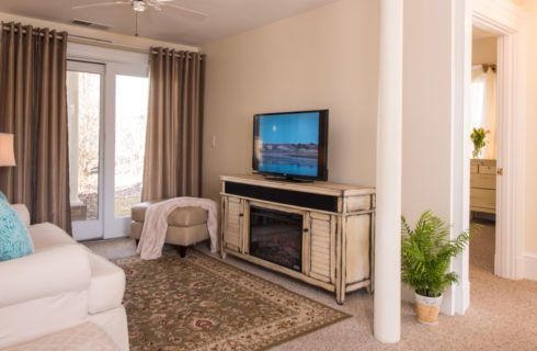 Sitting area with white upholstered love seat, light tan leather ottoman, distressed hutch with fireplace and flat-screen TV on top, and cream colored walls with white trim