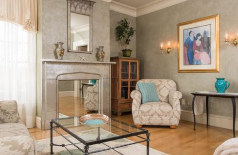 Sitting area with upholstered cream and taupe couch and chair, rod iron coffee table with glass top, rod iron end table with ornate lamp and blue vase, and a light stone fireplace converted to house a mirror