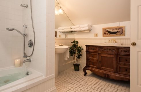 Bathroom with antique dark wooden dresser, white pedestal sink, and shower and tub combo unit surrounded by white tile