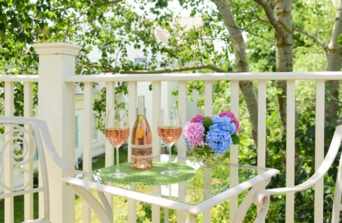 Wooden deck railing painted cream with rod iron table and chairs painted cream, bottle of wine, two wine glasses filled with wine, and glass vase with pink and purple flowers