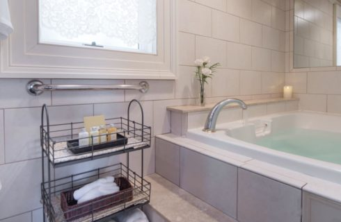 Light gray tiled walls and around large white tub with rod iron rack near by with soaps, rags, and towels