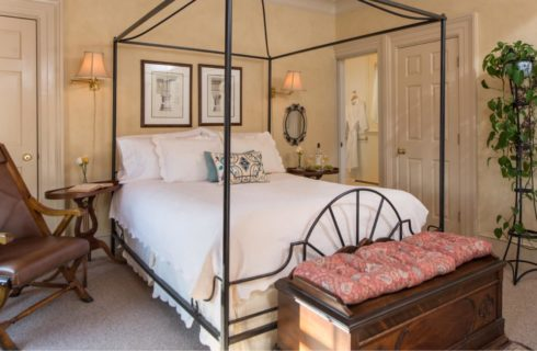 Bedroom with dark wooden furniture, rod iron bed with white bedding, wooden nightstands, yellow walls, and light colored carpeting