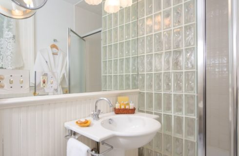 Bathroom with white paneling on the walls and glass block wall near the shower with a white pedestal sink