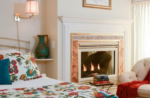 Bedroom with cream painted rod iron bed with floral and white bedding, sconce lamp attached to wall, burning fireplace with wooden mantel painted white, and upholstered chair