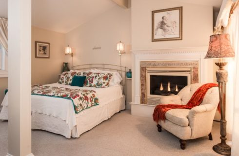 Bedroom with cream painted rod iron bed with floral and white bedding, sconce lamps attached to wall, burning fireplace with wooden mantel painted white, and upholstered chair