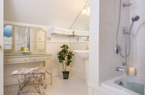 Bathroom with antique cream colored makeup table with rod iron bench, white sink, and shower and tub combo unit surrounded by white tile