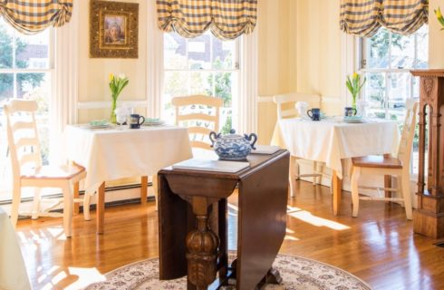 Dining area with wooden tables and chairs with white tablecloths, hardwood floors, crystal chandelier, and wooden ornate fireplace mantel