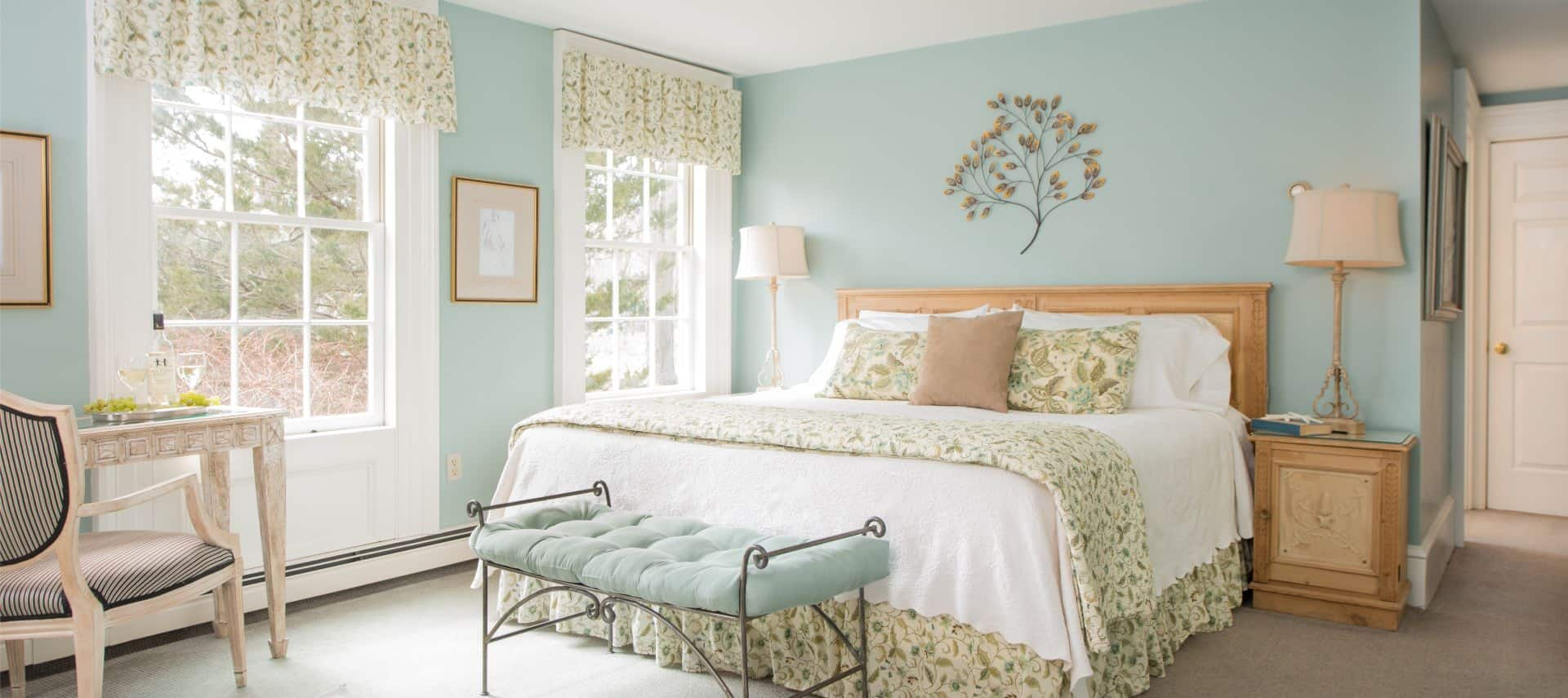 Bedroom with light mint walls and light colored carpeting, light wooden headboard with white and floral linens, rod iron bench with mint colored cushion, and light wooden nighttables with lamps
