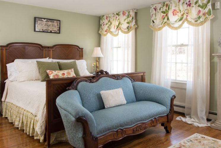 Bedroom with dark wooden furniture, cream and yellow bedding, ornate wooden love seat with blue upholstery, and sheer curtains