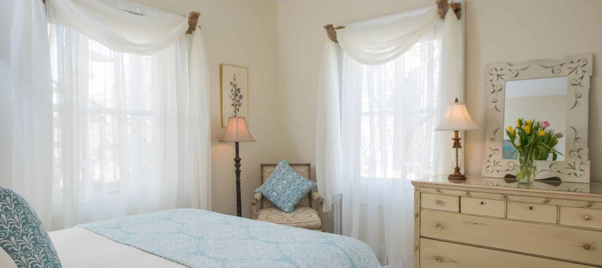 Bedroom with white and light blue bedding, upholstered vintage chair, and light wooden antique dresser with lamp, mirror, and vase full of flowers on top