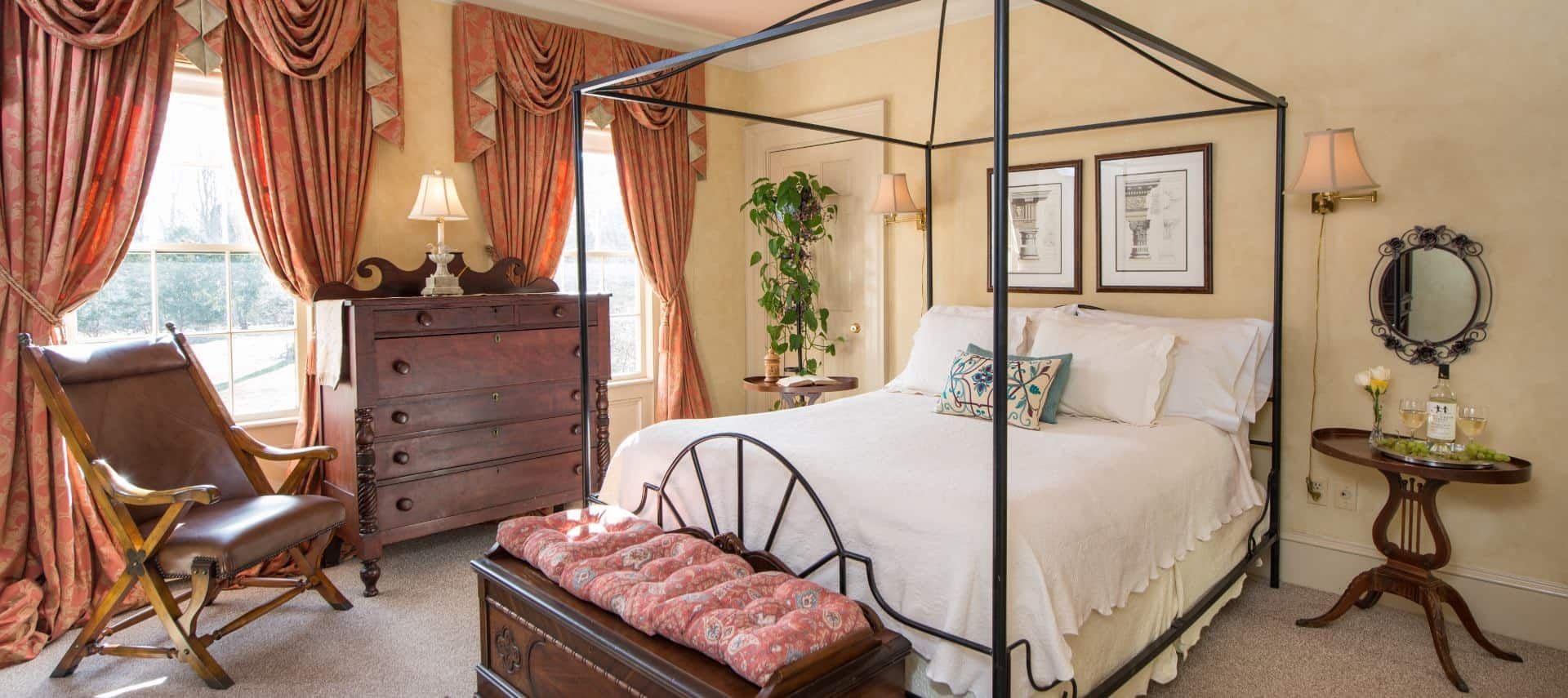 Bedroom with dark wooden furniture, rod iron bed with white bedding, wooden nightstands, yellow walls, light colored carpeting, and salmon colored drapery