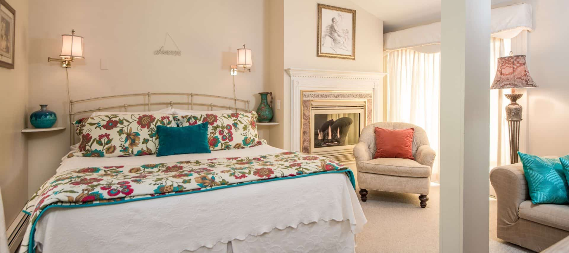 Bedroom with cream painted rod iron bed with floral and white bedding, sconce lamps attached to wall, burning fireplace with wooden mantel painted white, and upholstered chair and loveseat