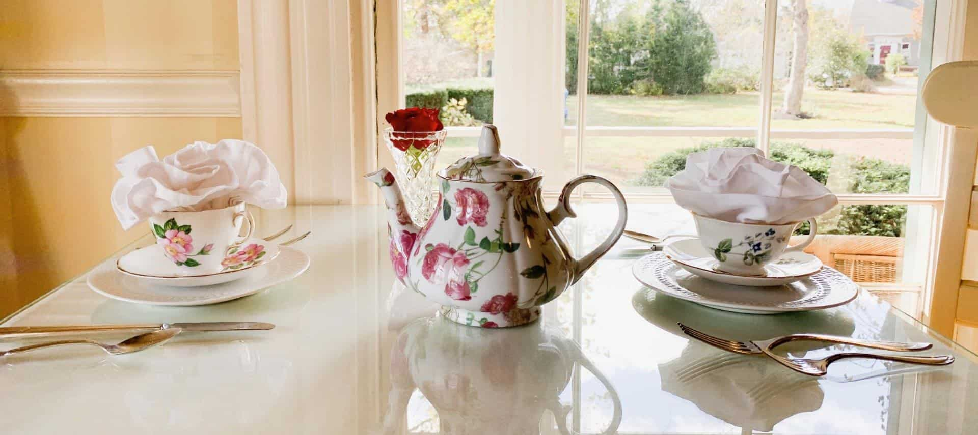 Table with two tea cups and saucers and teapot decorated with pink flowers and green stems