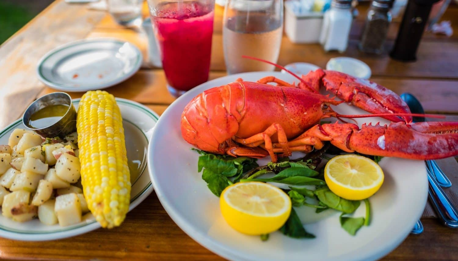 bright red lobster on a plate with greens and lemon beside an ear of yellow corn on the cob