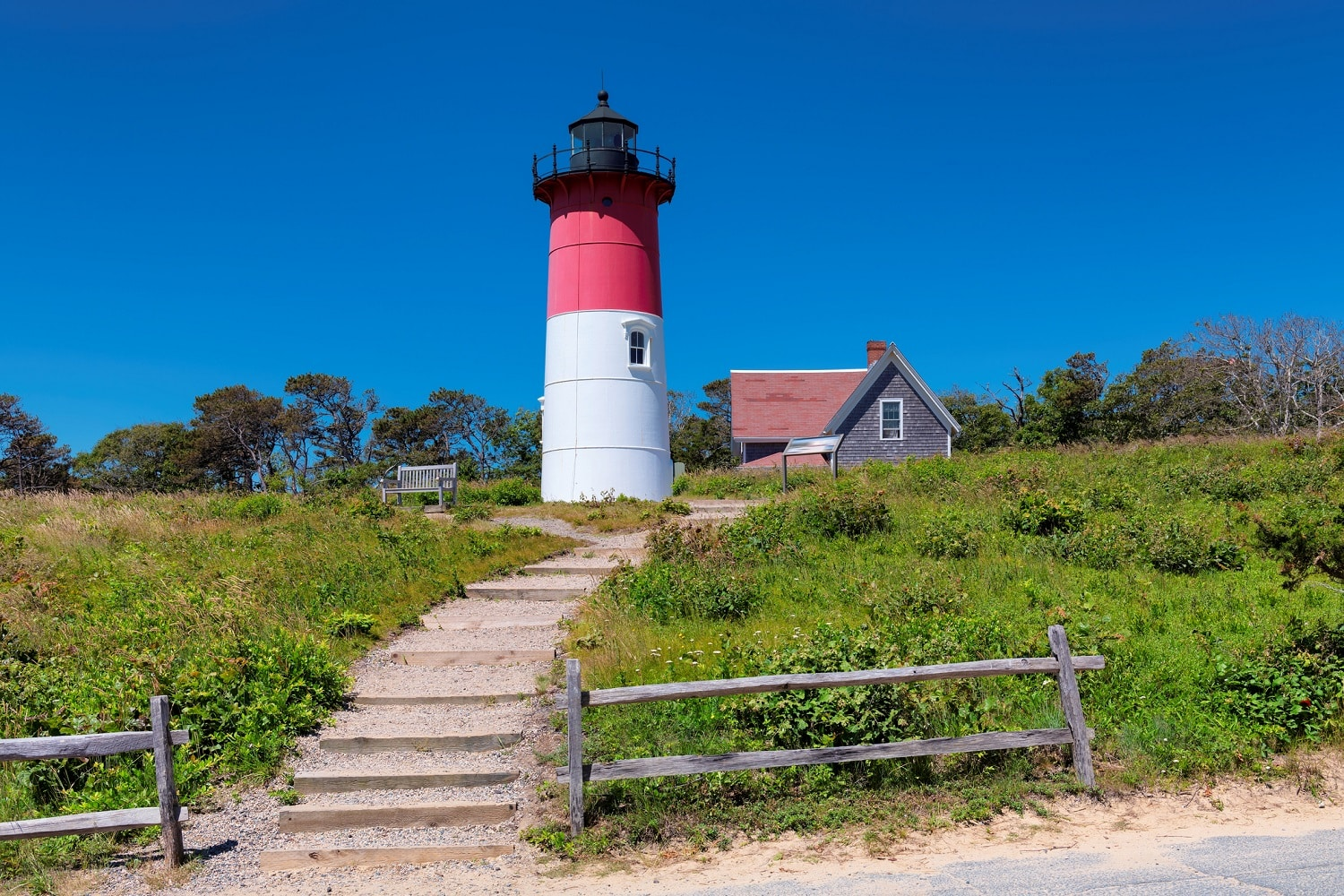 steps leading to a red, white and black lighthouse against a blue sky